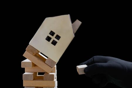 hand with black glove damaging the foundation of a house and the house is falling down Stock Photo