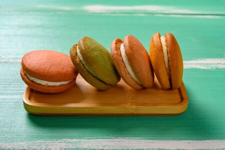 side view multi-color macaroon on a green wood table