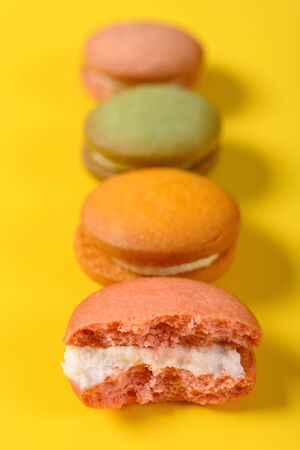 colorful macaroons and the front one with half eaten on yellow background 写真素材