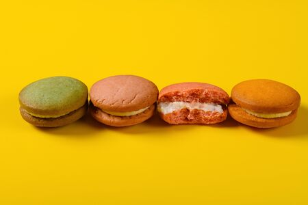 colorful macaroons with one piece half eaten on yellow background