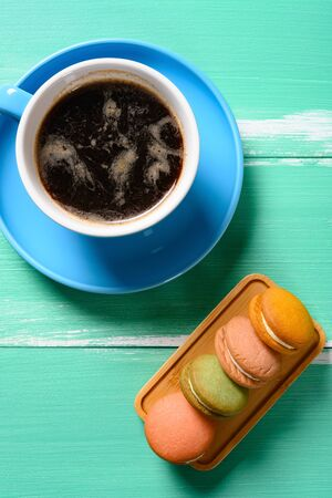 top view multi-color macaroon and cup of coffee vertical composition