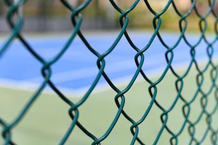 tennis court behind wire fence