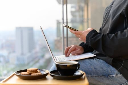 casual wearing man operating smartphone and laptop with coffee and cookies nearby on the balcony concept of work from home