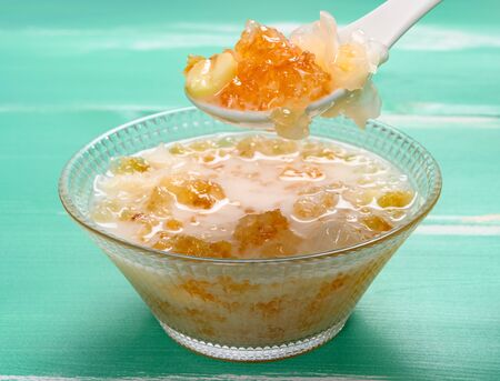 spoon taking out healthy syrup of peach gum and white fungus and lotus seeds