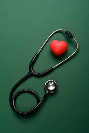 top view heart and stethoscope on a green background