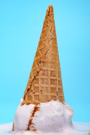 sweet potato flavor ice cream cone upside down and melted on blue background close up 版權商用圖片