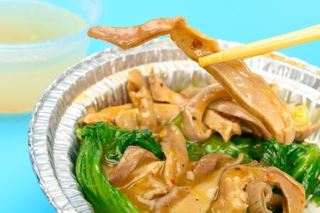 chopsticks taking out piece of pig stomach from bowl of fast food horizontal composition