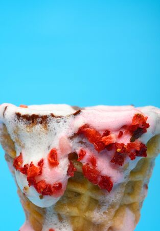 vanilla and strawberry flavor ice cream cone in a melting process close up on blue background