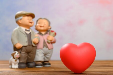 a red heart and smiling elder couple on background 免版税图像