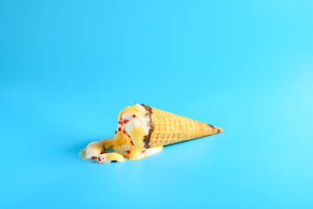 pineapple and cherry flavor ice cream cone in a melting process on a blue background