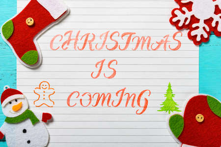 paper written with Christmas is coming and some decorations Stock Photo