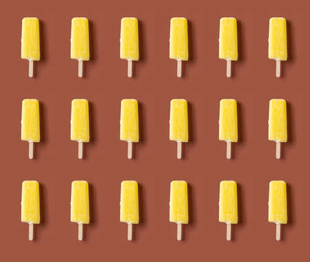 seamless yellow ice pops on a brown background