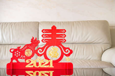 ox mascot and symbol of spring as symbol of Chinese New Year of the Ox in front of a sofa the Chinese means spring and good luck
