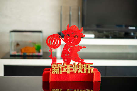 ox mascot with a lantern in a living room as symbol of Chinese New Year of the Ox 2021 translation of the Chinese characters -happy Chinese new year