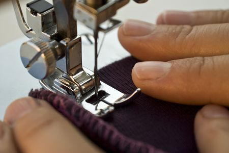 Sewing machine foot close-up with womans hands keeping a piece of fabric to sew. Stock Photo