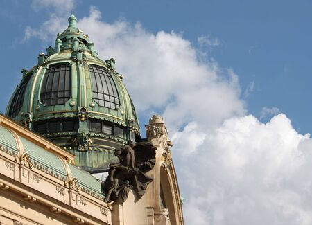 A close up of a theater in Prague with a green dome. Shot on a clear sunny day.