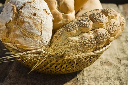 A close-up of a bread basket with a variety of breads and wheat on stone table.     Stock Photo