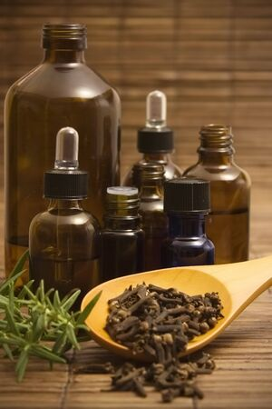 Essential oil bottles with fresh rosemary and a spoon of dried cloves on a bamboo .