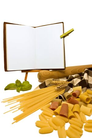 A close up of various pasta and wheat with a rolling pin and table cloth on the right side with fresh basil and an open blank recipe book ideal for copy space.On a white background.