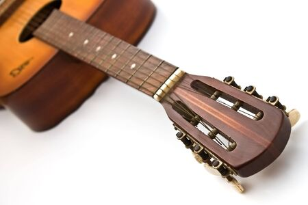 The headstock and fretboard of a wooden acoustic guitar.  Stock Photo