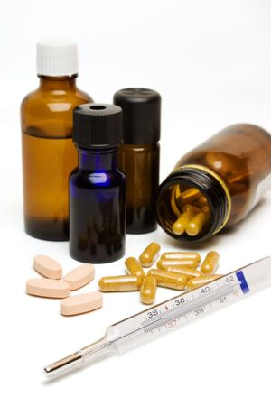Essential oil bottles, capsules, pills and a thermometer.