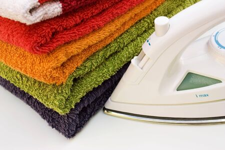 An iron with a stack of colorful towels on a white background.
