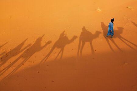 Berber man walking in Saharan desert. photo