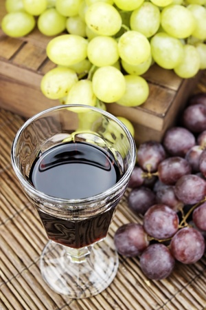 Glass of red wine with some grapes.