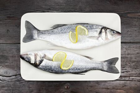 Fresh sea bass in a white plate, on a wooden surface. photo
