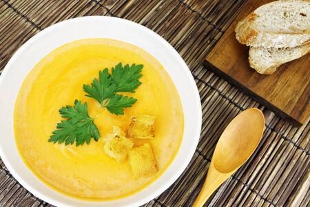A delicious carrot soup served with bread on a bamboo mat. Stock Photo