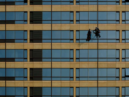 steeplejack: Two men clean the high-rise building which is a very dangerous work. Editorial