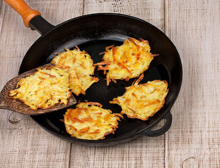Golden potato fritters on old cast iron frying pan 写真素材