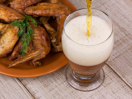 real ale: Beer and chicken wings on wooden background