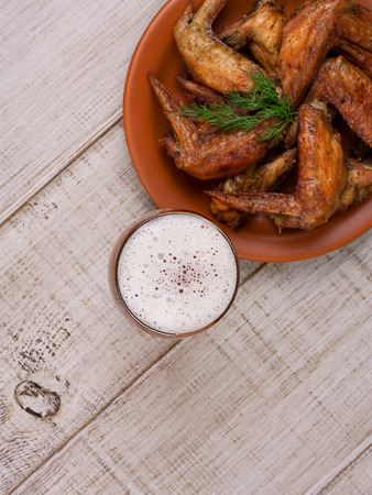 real ale: Beer and chicken wings on wooden background, top shot Stock Photo