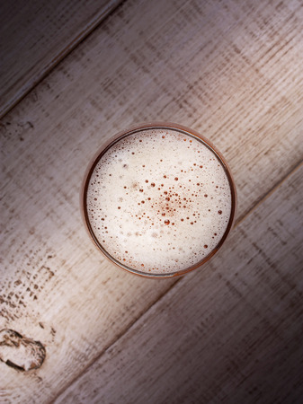 real ale: Glass of beer over wooden background, top shot