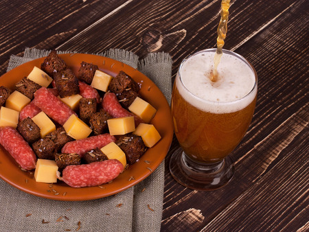 real ale: Beer with cheese and sausage plate on wooden background Stock Photo