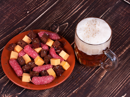 real ale: Glass of beer, cheese and smoked sausages plate