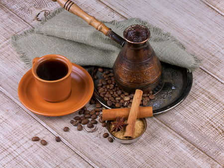 Coffee turk and cup of coffee on wooden background photo