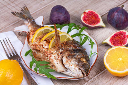 sea bream: Whole grilled fish dorado served with lemon and figs;