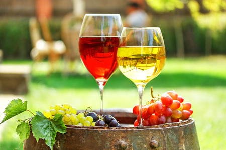 winetasting: Glasses of wine on old barrel with iron rings in a garden