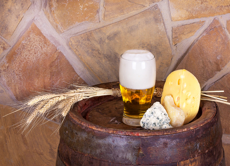real ale: Glass of beer, cheese and ears on old barrel with iron rings