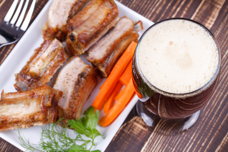real ale: Glass of beer, grilled pork ribs and fresh carrot on wooden background