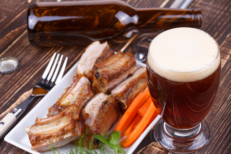real ale: Glass and bottle of beer. Grilled pork ribs and fresh carrot on wooden background