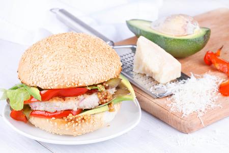 sesame seed bun: Burger with turkey, avocado, lettuce, onions, red paprika pepper on a sesame seed bun