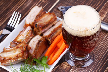 mild: Glass of beer, grilled pork ribs and fresh carrot on wooden background