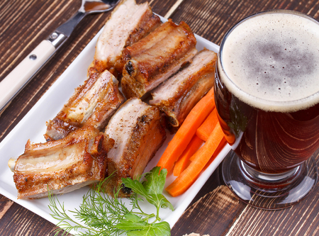 real ale: Grilled pork ribs and glass of beer on wooden background