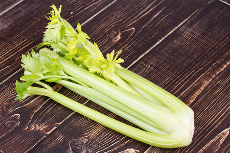 Organic vegetables - celery with leaves on wooden background