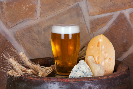 Glass of beer, cheese and ears on old barrel with iron rings