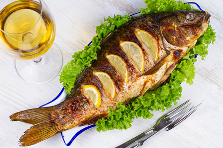 Whole grilled fish carp served with salad and lemon; glass of wine 写真素材