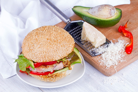 sesame seed bun: Home cooked burger with turkey, avocado, lettuce, onions, red paprika pepper on a sesame seed bun